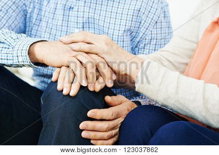 Senior couple holding hands at home for comfort