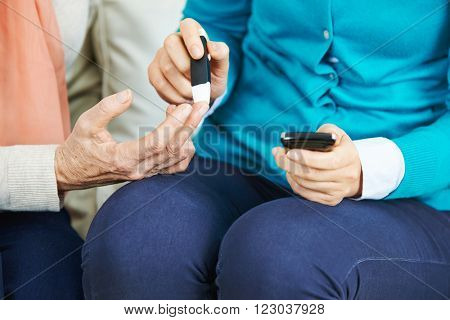 Blood test on finger of senior woman with diabetes mellitus