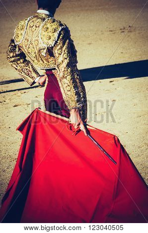 bullfighter standing and holding the capote. Matador in the bullring