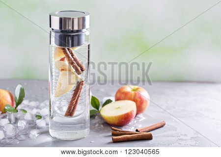 Infused water with apple and cinnamon in a bottle