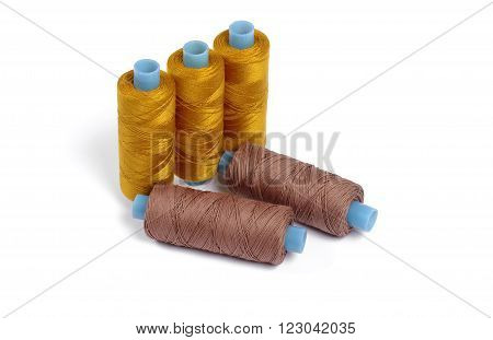 Five sewing spools on white backgrouns - brown and orange