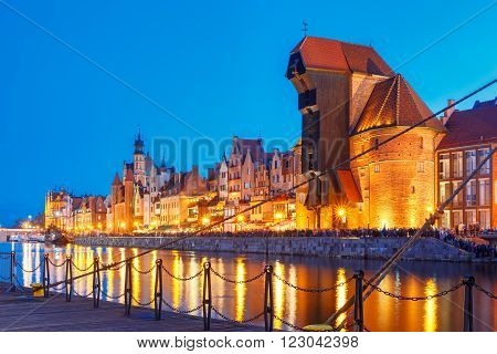 Old harbour crane and city gate Zuraw in old town of Gdansk, Dlugie Pobrzeze and Motlawa River at night, Poland