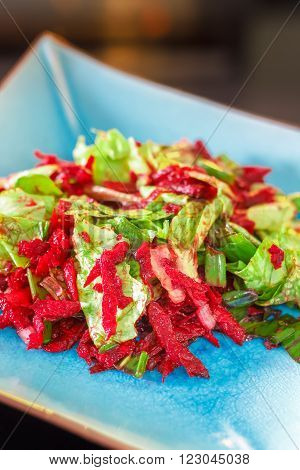 Lettuce and beetroot salad served on blue plate with scallion ramsons lemon and olive oil