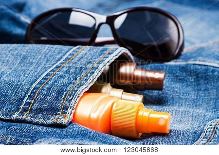 Cosmetic sunscreen products in jeans pocket on the background of sunglasses. Skin care cosmetics containing sun protection factor