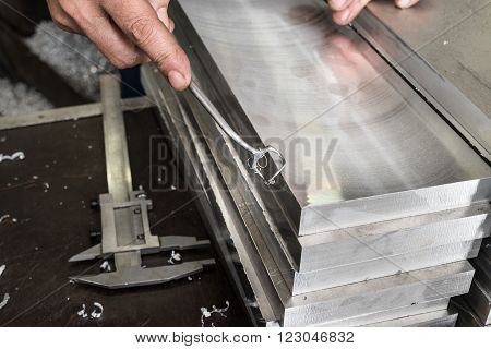Deburring of steel plates after milling. In his hand a simple cutter.