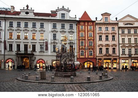 PRAGUE, CZECH REPUBLIC - FEBRUARY 13, 2016: Tourists walk around the historic homes in the evening on the square called Male namesti