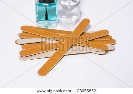 Cardboard nail files and clear nail polish on a white background ** Note: Shallow depth of field