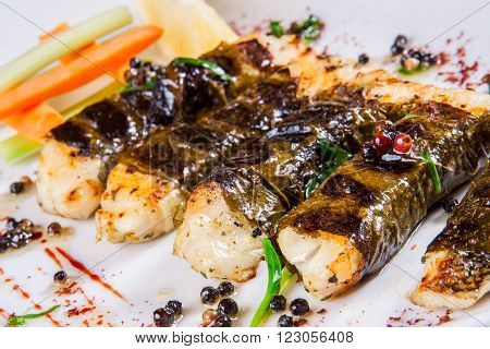 Pikeperch baked in grape leaves on white plate