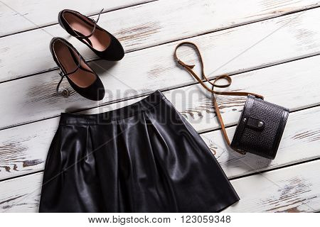 Woman's dark skirt and footwear. Fashion clothes on wooden background. Tiny handbag and evening footwear. Suede frosted shoes and skirt.