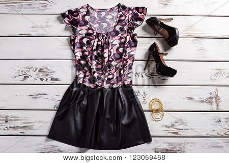 Female clothes and heel shoes. Woman's trendy outfit on shelf. Dark outfit and yellow bracelets. Clothing and small bright accessories.