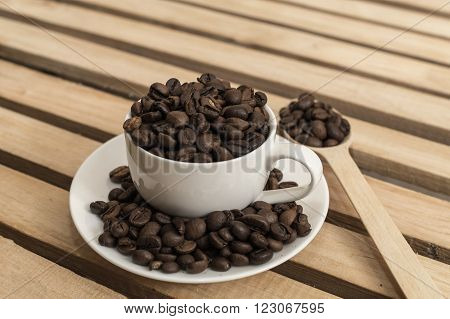 Fragrant coffee beans poured into the Cup and on the saucer.