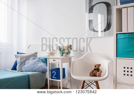 Seaside decorations on nightstand near blue single bed in modern children's room