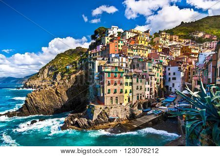 Riomaggiore fisherman village in a dramatic windy weather. Riomaggiore is one of five famous colorful villages of Cinque Terre in Italy, suspended between sea and land on sheer cliffs upon the  turquoise sea.