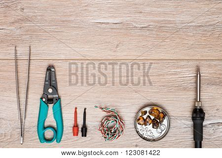 Tool kit for soldering on a wooden table. Electric soldering iron tweezers clips stripping tool solder and rosin in a can.