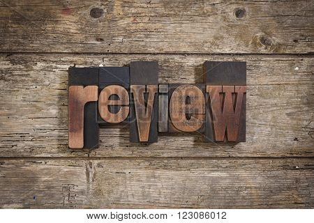 review, single word set with vintage letterpress printing blocks on rustic wooden background