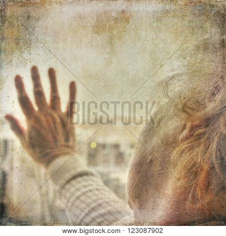 elderly woman with arm extended on a window and in deep thoughts