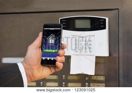 Close-up Of Businessperson Hand Holding Smartphone For Arming The System