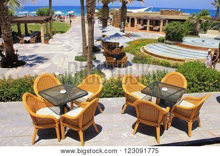 CRETE, GREECE - JULY 23, 2015: Summer view with mediterranean hotel resort and al fresco wicker seats on the terrace, Crete, Greece