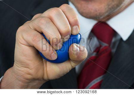 Businessperson Pressing Stressball In Hand