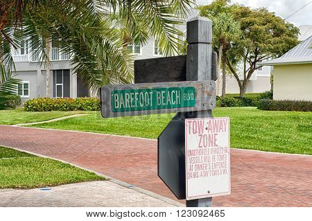 Old weathered Barefoot Beach Blvd wooden sign with Tow Away Zone sign along brick paver street in Bonita Springs Florida.