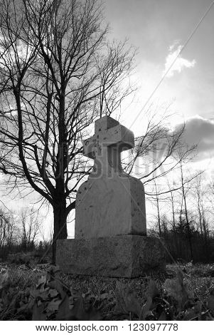An old tombstone in a quiet gravesite with the sunshine backlighting the cross in a spirtual manner.