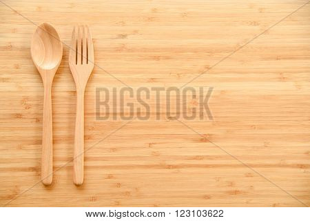 Wooden spoon and fork on wood texture of dining table from top view - use for background in kitchen and food concept