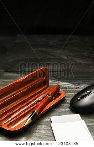 Closeup of a pen and pencil set in wooden case, a computer mouse and security card on a slate surface. Vertical format with copy space.