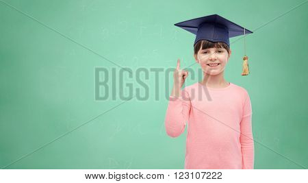 childhood, school, education, learning and people concept - happy girl with in bachelor hat or mortarboard over green school chalk board background