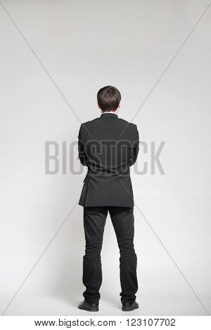 Businessman isolated on white and looking on empty wall
