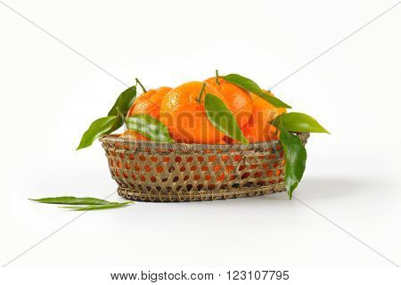 scuttle of ripe tangerines on white background