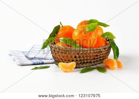 scuttle of ripe tangerines and checkered dishtowel on white background