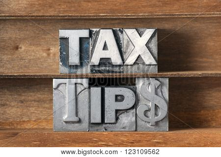 tax tips phrase made from metallic letterpress type on wooden tray