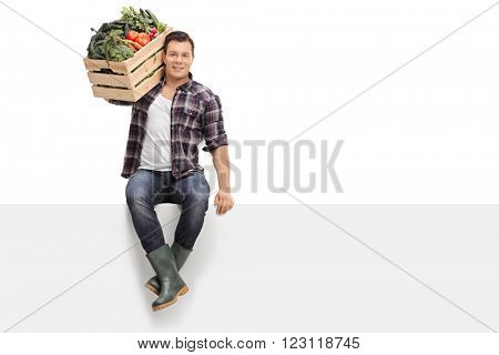 Young farmer carrying a crate full of vegetables on his shoulder seated on a blank panel isolated on white background