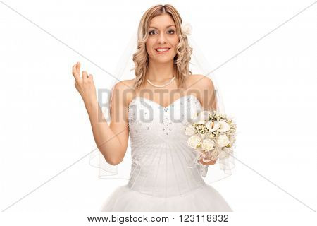 Young bride smiling and wishing luck with her fingers crossed isolated on white background