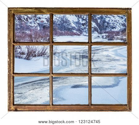 Frozen mountain river as seen  through vintage, grunge, sash window with dirty glass