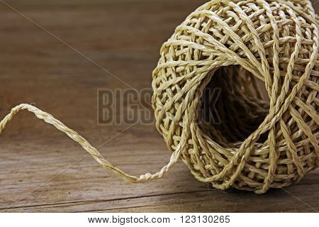 Ball of string with texture and strands on a wooden background close up shot selected focus