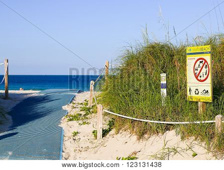 MIAMI BEACH, USA - MAY 9, 2015: Path leading to the beach with a prohibition sign showing not permitted activities on the beach, in the back some people swimming.