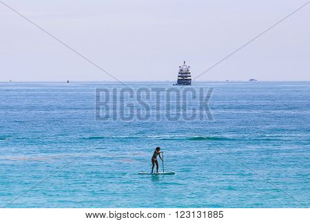 MIAMI BEACH, USA - MAY 9, 2015: A woman doing standup paddleboarding near the entrance of the Port of Miami in the back several yachts.