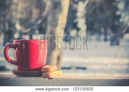 Red coffee tea mug cup with butter shortbread biscuits in winter morning glowing sun washed blue matter