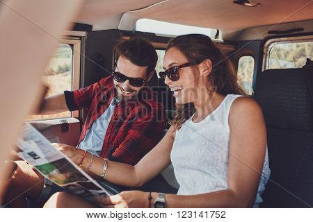 Happy young couple planning their travels together reading a map while sitting in their car. Smiling man and woman using map on roadtrip.
