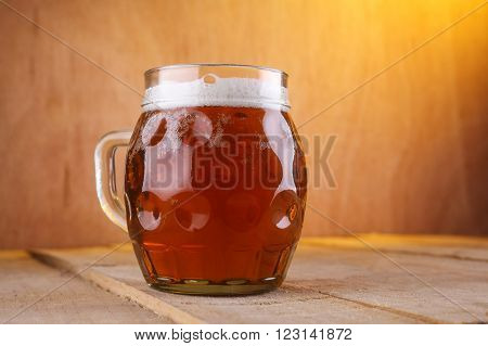 Dimpled mug with amber beer on a grunge wood surface