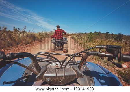 View from a quad bike in nature. Man in front driving off road on an all terrain vehicle. POV shot.