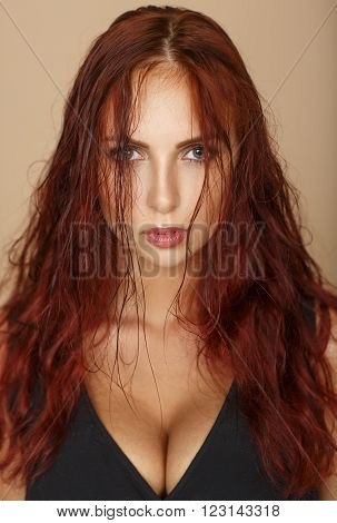 Portrait of red-haired beautiful woman with big breasts. Disheveled hair. Look into the camera. Beauty ginger.