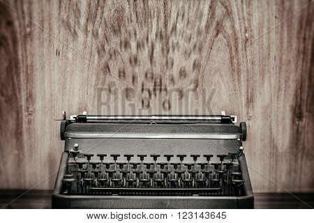 Vintage typewriter with flying letters on the background, suggesting inspiration