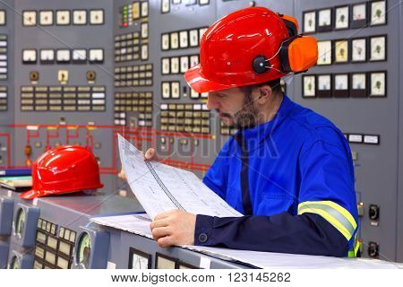 Engineer working in the industrial interior.Manufacture and sale of electrical energy on an industrial scale.