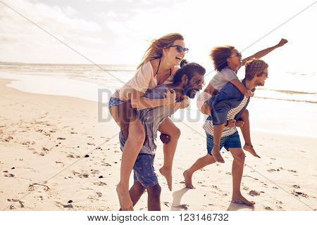 Two young men giving their girlfriends piggyback rides at the beach. Cheerful young friends enjoying summertime on the beach.