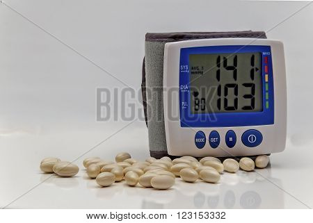 Showing a blood pressure machine showing medium to high blood pressure on the lcd display and pills shown on a table