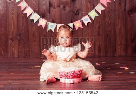 Funny child girl 1 year old sitting with birthday cake on wooden floor in room. Looking at camera. Childhood. ** Note: Soft Focus at 100%, best at smaller sizes