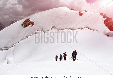 Four People with Climbing Gear Linked Belay Rope Walking Up on Snowfield Glacier Towards High Altitude Mountain Pass Shining Sun Summits on Background