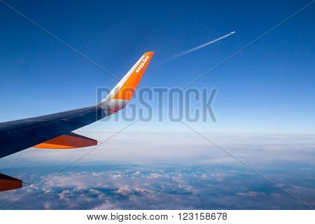 UK. LONDON DECEMBER 14. 2014: Easy Jet flying above the clouds. The second plane fly away. Easyjet is a British airline operator.